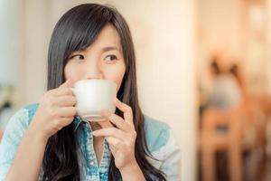 giovane donna asiatica felice che si siede in caffè dell'annata foto