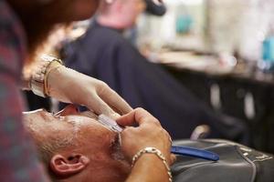 cliente di rasatura del barbiere con il rasoio della gola tagliato foto