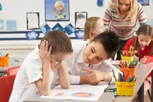 gruppo di scolari primari e insegnante che lavora alla scrivania foto