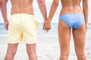 coppia felice mano nella mano e guardando il mare foto