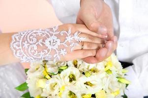 il primo piano delle mani dello sposo e della sposa foto