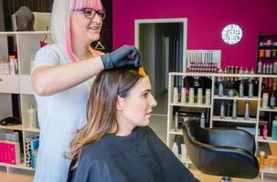 parrucchiere che mostra campione di tintura per capelli alla giovane donna foto