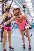 personal trainer che insegna alla donna in allenamento in sospensione foto