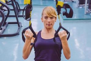 donna che fa allenamento in sospensione con cinghie di fitness foto