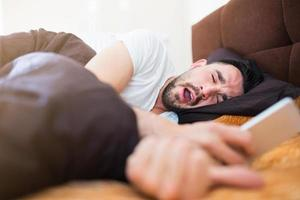 pigra mattina a letto con smart phone foto