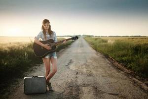 ragazza del hippie del viaggiatore con la chitarra foto
