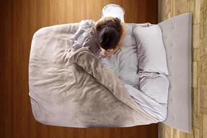 vista dall'alto di una giovane donna che prega in camera da letto foto