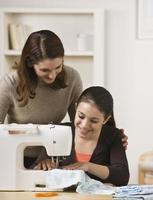 madre che guarda la figlia usare la macchina da cucire foto