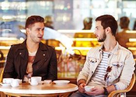 due giovani uomini / studenti che utilizzano computer tablet nella caffetteria foto