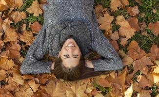 autunno nel parco, giovane donna sorridente rilassante nella natura foto