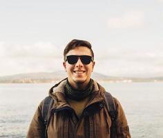 uomo bello sorridente sulla costa foto