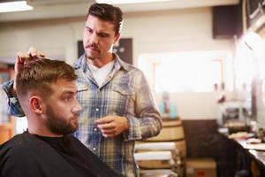 barbiere maschio che dà taglio di capelli del cliente in negozio foto