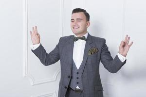 uomo elegante in un abito grigio, cravatta a farfalla in piedi con foto