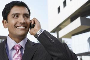uomo d'affari che per mezzo del telefono cellulare davanti alla costruzione foto