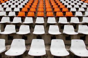 davanti ai sedili bianchi e arancioni dello stadio foto