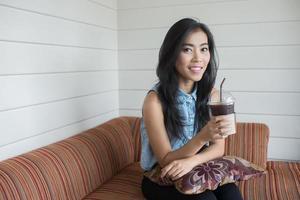 donna asiatica che si siede nella caffetteria foto