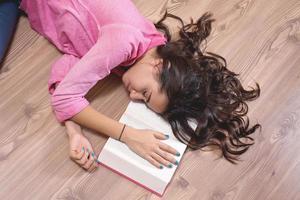 giovane studentessa che dorme nel parquet con il libro. foto