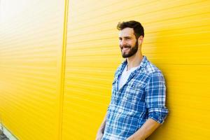 bel giovane con le cuffie sul muro giallo