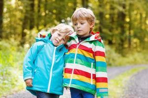 due ragazzini di pari livello con impermeabili colorati e stivali che camminano foto