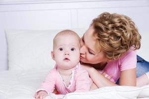 bella mamma che bacia bambino attraente