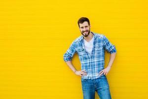 giovane uomo felice in piedi contro un muro giallo foto