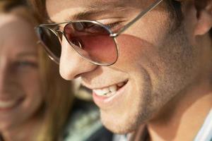 giovane sorridente che indossa occhiali da sole foto