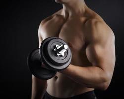 bell'uomo muscoloso, lavorando con manubri foto