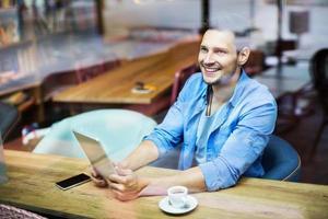 uomo che per mezzo della compressa digitale al caffè foto