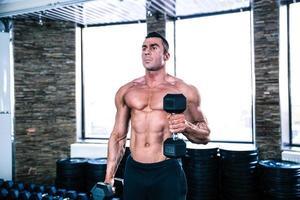 allenamento uomo muscoloso con manubri