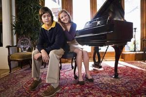 bambini seduti su una panca per pianoforte foto