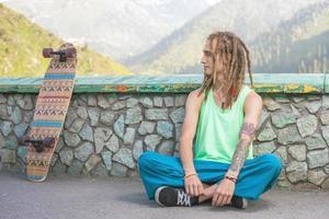 Ritratto di uomo bello freddo, divertente con skateboard in montagna
