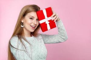 ragazza gioiosa confezione regalo sfondo rosa, giorno di san valentino, festa della donna foto