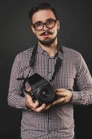 bel ragazzo con la barba che tiene la macchina fotografica d'epoca foto