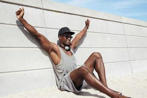 giovane muscolare che si siede sulla spiaggia che sembra felice foto