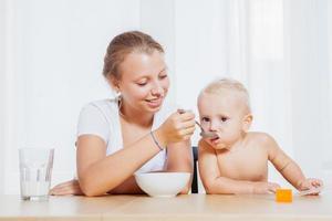 sorella maggiore che dà da mangiare al suo fratellino con la colazione foto