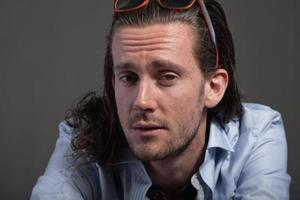 capelli lunghi uomo cool con viso espressivo che indossa una camicia blu. foto