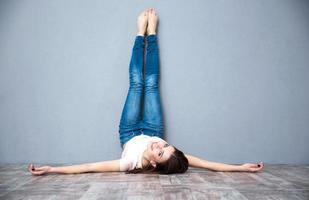 donna sdraiata sul pavimento con le gambe sollevate foto