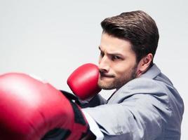uomo d'affari in guantoni da boxe colpire alla macchina fotografica foto