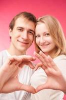 coppia facendo forma di cuore con le mani foto