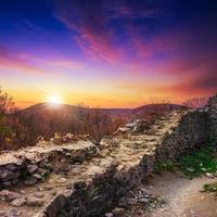 rovine di un antico castello nelle montagne serali foto
