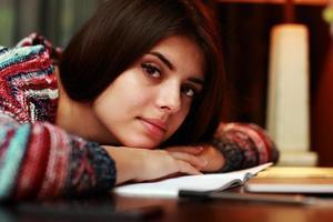 donna sdraiata sul tavolo con il notebook foto