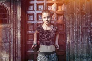 ragazza adolescente di fronte a un antico ingresso