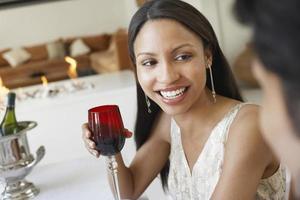 donna che tiene il bicchiere di vino rosso alla cena foto