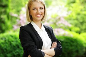 donna sorridente in piedi con le braccia conserte i foto