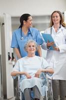 infermiera che spinge paziente in un corridoio foto