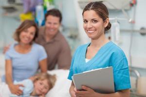 infermiera in possesso di un appunti accanto alla famiglia foto