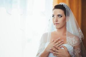 bella sposa si prepara in abito da sposa bianco con acconciatura foto
