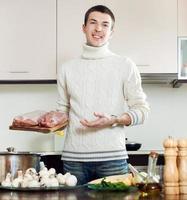 uomo giovane e felice che tiene carne in cucina