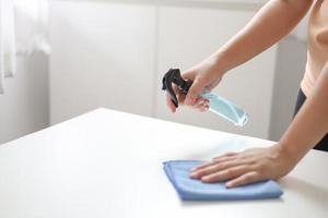 donna che spruzza detergente sul piano di lavoro foto