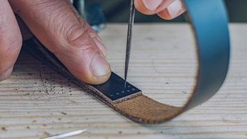 artigiano che fa un cinturino in pelle nera foto